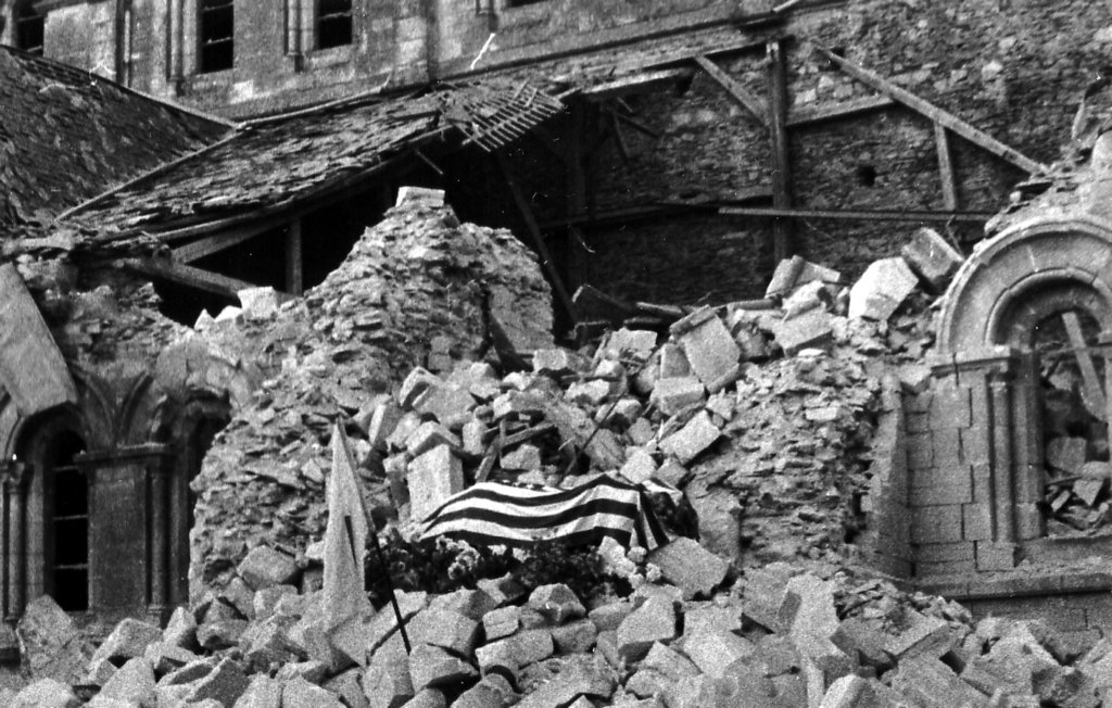 Major Howie under the USA flag, on the rubble of Le Croix church