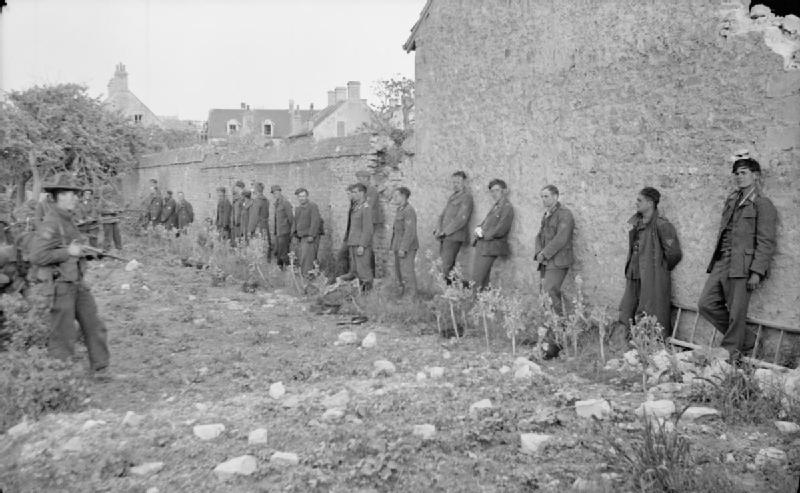 German prisoners captured by Canadian troops lined up against a wall at Saint-Aubin-sur-Mer, 6-7 June 1944