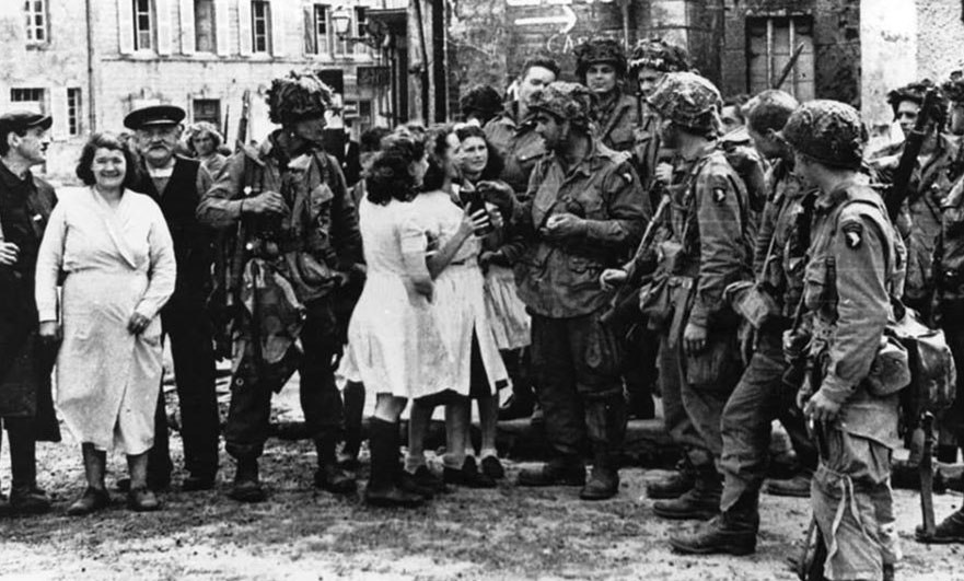 Airborne troops (see the Screaming Eagle badges) after the liberation in the central square of Sainte-Marie-du-Mont