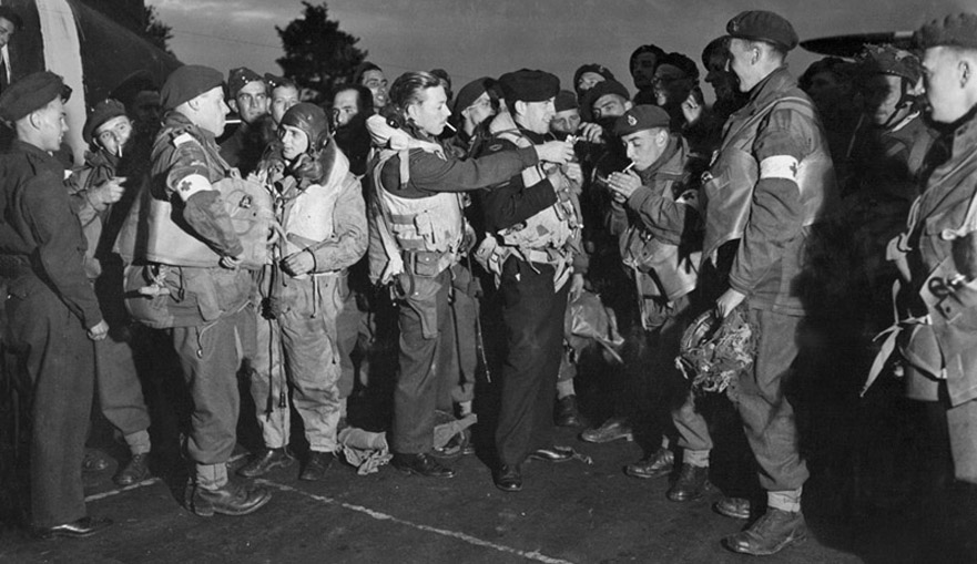 Paratroopers of 6th Airborne Division, including members of the Parachute Ambulance units, enjoy a last cigarette with RAF aircrew before boarding their transport June 1944