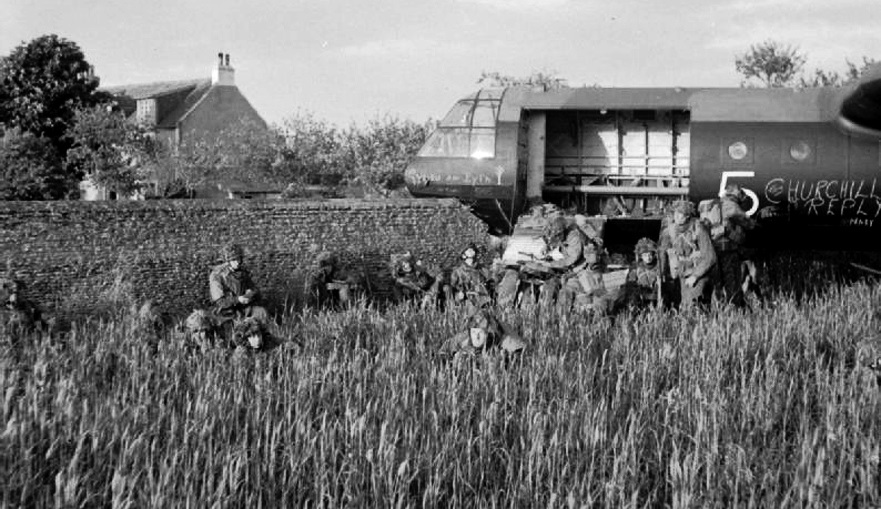 Glider troops beside their Horsa glider, which crashed through a stone wall during its landing on 6th Airborne Division's drop zone near Ranville, 6 June 1944